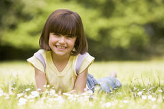 Young girl lying outdoors smiling Royalty Free Stock Image