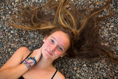 Young girl lying on the river pebbles with scattered hair. Top view Stock Photography