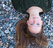 Young girl lying on the river pebbles, top view closeup portrait. Stock Images