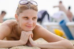 Young girl lying on sandy beach against the backdrop of other travelers and smiling looks into the distance Stock Photography