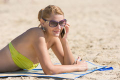Young girl lying on the sandy beach and happily talking on the phone Stock Photography