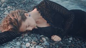 A young girl lying on the seashore unconscious, without movement. Unrecognizable woman lies face down on the shore. A young girl lying on the seashore stock video footage