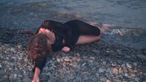 A young girl lying on the seashore unconscious, without movement. Unrecognizable woman lies face down on the shore. A young girl lying on the seashore stock video
