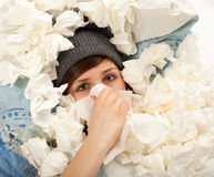 The girl is lying sick in bed and blowing her nose Royalty Free Stock Image