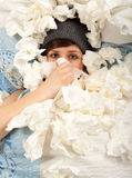 The girl is lying sick in bed and blowing her nose Royalty Free Stock Photo