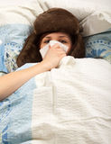 The girl is lying sick in bed and blowing her nose Stock Image