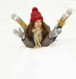 Young girl lying in the snow and laughs Stock Photo
