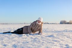 Young girl is lying on a snowy Royalty Free Stock Image