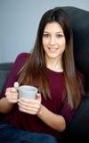 Young girl lying on the sofa drinking tea Stock Photos