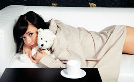 The young girl lying on a sofa with teddy bear toy royalty free stock photos