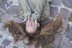 Young girl lying on the stone pavement with scattered hair. Royalty Free Stock Photo
