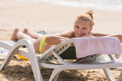 Young girl lying on a sun lounger on beach with a smile looks in the frame Royalty Free Stock Photo
