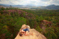 Young girl lying on top of the rock in the canyon royalty free stock images