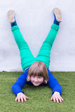Young girl lying upside down against wall Royalty Free Stock Image