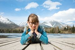Young girl is lying on wooden boards in mountains near lake. Thoughtful gesture stock image