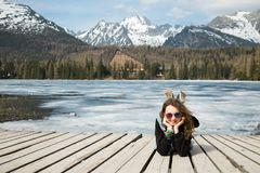 Young girl is lying on wooden terrace by frozen mountains lake S stock photo