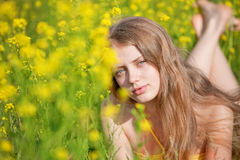 Young girl lying in yellow flowers on spring meado Royalty Free Stock Image