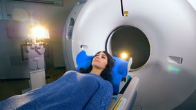 Young girl on a magnetic resonance imaging MRI scanner in a modern hospital. Magnetic resonance imaging MRI scanner in a modern hospital. 4K