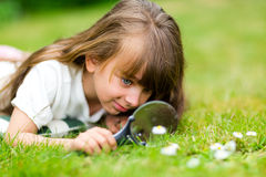 Young girl with magnifier Stock Images