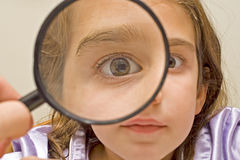 Young girl and magnifying glass Royalty Free Stock Images