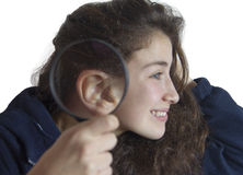 Young girl with a magnifying glass next to her ear Stock Photo