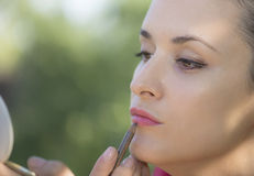Young girl make up. A young girl make up her lips royalty free stock photography