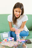 Young girl makes decorative bracelet Stock Images