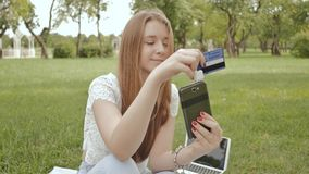 A young girl makes a payment in an online bank using a mini magnetic mobile card reader. A young girl makes a payment in an online bank using a mini magnetic stock video