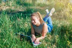 A young girl makes purchases in the online store through the computer lying on the green grass. stock photo