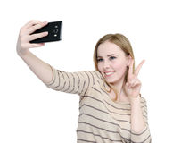 Young girl makes selfie on a smartphone, isolated on white background Stock Images