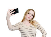 Young girl makes selfie on a smartphone, isolated on white background Royalty Free Stock Photos