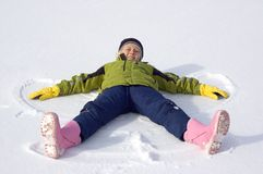 Young Girl Makes a Snow Angel. Cute young girl dressed in colorful winter clothes makes a snow angel Royalty Free Stock Image