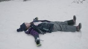 A young girl makes a snow angel by lying on her back in the snow and moving her arms and legs. Slow motion stock video footage