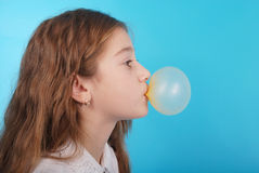 Young girl making a big bubble with a chewing gum Royalty Free Stock Photos