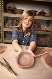 Young girl making bowl in clay studio Stock Images