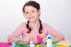 Young girl making craft card. Child cutouts silhouettes from colored paper, arranges pieces and glues them together royalty free stock images
