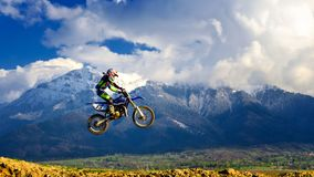 Young girl with motocross bike in Romania. Extreme sports. Young girl making extreme motocross in the spring time. In the background is Bucegi mountains with royalty free stock image