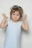 Young girl making faces. Cute young girl in sun glasses Stock Image