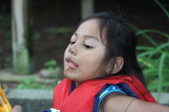 Young Girl making Faces. Cute young girl with scratches on her nose and lip from a fall, having fun by making faces, sticking her tongue out Stock Photos
