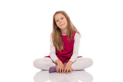 Young girl making faces on the floor. Portrait of a young girl with long hair sitting with crossed legs on the floor and making faces. Isolated on white Royalty Free Stock Images