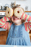 Young Girl Making Glasses With Colourful Doughnuts stock photo