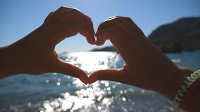 Young girl making heart shape with her hands over sea background on a sunny day. Summer holidays on the beach. Concept. Of vacation. Close up stock video footage