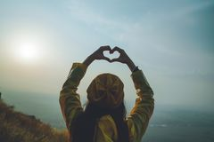 A young girl making heart symbol with her hands at sunset Royalty Free Stock Photos