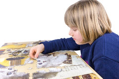 Young girl making jigsaw puzzle on table. Young girl laying jigsaw puzzle on table isolated on white background Stock Photography