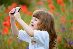 Young girl making a photo on the cell phone outdoor Royalty Free Stock Image