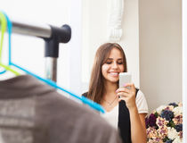Young girl making photo with mobile camera in shop Stock Photography