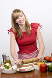 Young girl making pizza. Beautiful young girl making pizza royalty free stock image