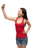 Young girl making selfie through cellphone. Happy young girl making funny face while taking pictures of herself through cellphone, over white background Stock Image