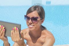 Young girl making selfie by the pool with a tablet Royalty Free Stock Image