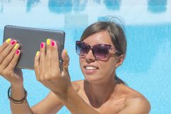 Young girl making selfie by the pool with a tablet Stock Photography